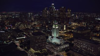 AX0158_102 - 8K stock footage aerial video orbiting City Hall at night near skyscrapers in Downtown Los Angeles, California