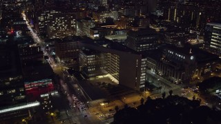 AX0158_103 - 8K stock footage aerial video flying by City Hall and approach LAPD headquarters at night in Downtown Los Angeles, California