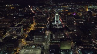 AX0158_105 - 8K stock footage aerial video of a reverse view of Los Angeles City Hall at night in Downtown Los Angeles, California