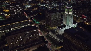 AX0158_107 - 8K stock footage aerial video flying away from LA City Hall at night in Downtown Los Angeles, California