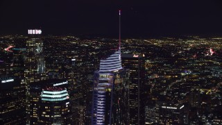 AX0158_113 - 8K stock footage aerial video circling the top of Wilshire Grand Center at night in Downtown Los Angeles, California