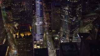 AX0158_117 - 8K stock footage aerial video revealing Wilshire Blvd and base of Wilshire Grand Center at night, Downtown Los Angeles, California