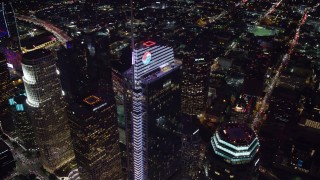 AX0158_122 - 8K stock footage aerial video orbiting and tilt to a bird's eye of Wilshire Grand Center in Downtown Los Angeles, California at night