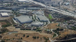 AX0159_009 - 8K stock footage aerial video flying away from warehouses along Interstate 5, Sylmar, California