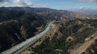 AX0159_010 - 8K stock footage aerial video following light traffic on I-5 through the mountains, Santa Clarita, California