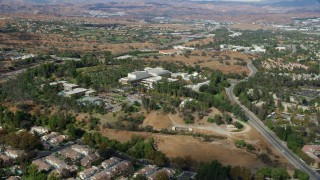 AX0159_023 - 8K stock footage aerial video of a wide shot of California Institute of the Arts nestled among suburban neighborhoods, Santa Clarita, California