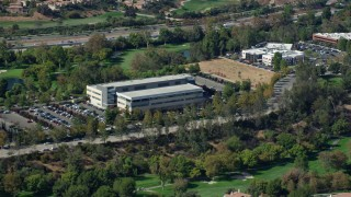 AX0159_030 - 8K stock footage aerial video of an office buildings along a golf course, Valencia, California