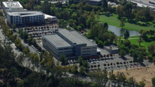 AX0159_031 - 8K stock footage aerial video orbiting an office building and parking lot next to a golf course, Valencia, California
