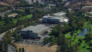 AX0159_032 - 8K stock footage aerial video orbiting office buildings next to a golf course, Valencia, California