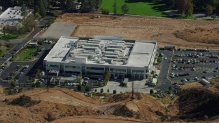 AX0159_039 - 8K stock footage aerial video orbiting a tech office building and parking lot, Valencia, California