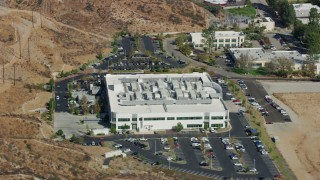 AX0159_040 - 8K stock footage aerial video orbiting to front of tech office building, Valencia, California