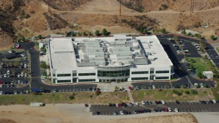 AX0159_041 - 8K stock footage aerial video passing by front of tech office building, Valencia, California