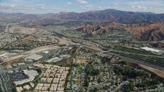 AX0159_050 - 8K stock footage aerial video flying over suburban housing toward highway and mountains, Santa Clarita, California