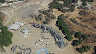 AX0159_054 - 8K stock footage aerial video orbiting away form old Wipe Out set and a dinosaur structure at Sable Ranch, Santa Clarita, California