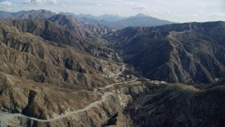 AX0159_055 - 8K stock footage aerial video flying over a road winding through the canyons, Newhall, California