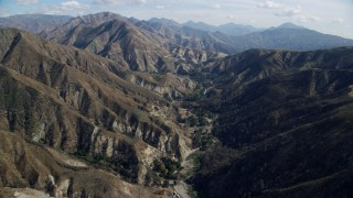AX0159_056 - 8K stock footage aerial video following a road in the canyons, Newhall, California