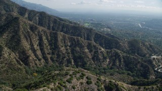 AX0159_063 - 8K stock footage aerial video flying over mountain ridges with a residential community in the distance, Tujunga, California