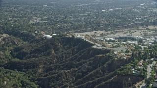 AX0159_066 - 8K stock footage aerial video approaching JPL from behind a mountain ridge, Pasadena, California