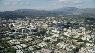 AX0159_097 - 8K stock footage aerial video orbiting city center and office buildings with mountains in the background, Pasadena, California