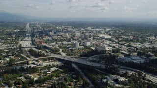 AX0159_104 - 8K stock footage aerial video approaching the 134 freeway, office buildings, and Pasadena City Hall in California