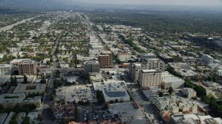 AX0159_107 - 8K stock footage aerial video flying over office and retail buildings to approach Pasadena City College, California