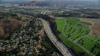 AX0159_131 - 8K stock footage aerial video following the I-10 freeway between homes and Forest Lawn Covina Hills Cemetery, Covina, California