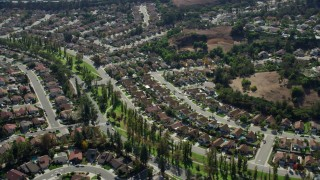 AX0159_134 - 8K stock footage aerial video flying by tract homes in a peaceful neighborhood in Pamona, California