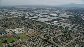 AX0159_136 - 8K stock footage aerial video flying over homes and Don Antonio High School, approach warehouses, Chino, California