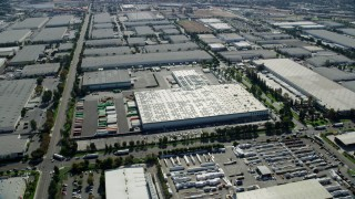 AX0159_138 - 8K stock footage aerial video flying over large warehouses in Chino, California
