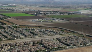 AX0159_139 - 8K stock footage aerial video flying over tract homes towards the East Yard of CIM Prison (California Institution for Men), Chino, California