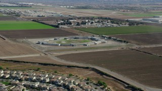 AX0159_140 - 8K stock footage aerial video flying over tract homes towards East yard CIM Prison (California Institution for Men) in Chino, California