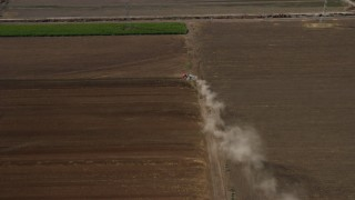 AX0159_150 - 8K stock footage aerial video of a truck creating dust trail in farmland, Chino, California