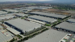 AX0159_151 - 8K stock footage aerial video of several large warehouse buildings in Chino, California