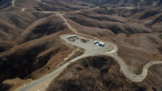 AX0159_154 - 8K stock footage aerial video flying over storage facility in the hills near dirt trails, Chino Hills State Park, California