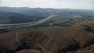 AX0159_155 - 8K stock footage aerial video flying over hills toward a highway and tract homes, Yorba Linda, California