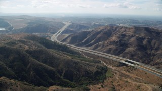 AX0159_159 - 8K stock footage aerial video of a freeway through the hills, Highway 241, Anaheim, California