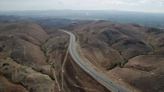 AX0159_162 - 8K stock footage aerial video following a freeway through the hills, Irvine, California