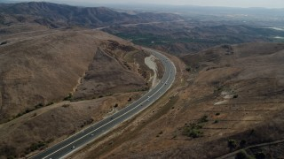 AX0159_163 - 8K stock footage aerial video following a freeway with light traffic through the hills, Irvine, California