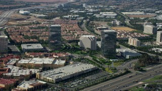 AX0159_168 - 8K stock footage aerial video of office buildings and shopping mall along a freeway, Irvine, California