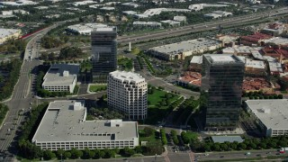 AX0159_172 - 8K stock footage aerial video orbiting office buildings along Alton Parkway, Irvine, California