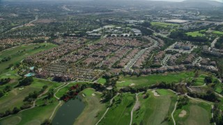 AX0159_177 - 8K stock footage aerial video flying over golf course and tract homes, Aliso Viejo, California