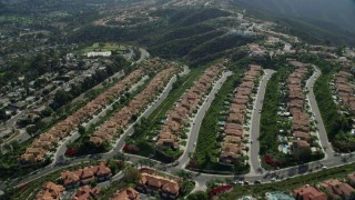 AX0159_182 - 8K stock footage aerial video approaching and flying over homes on green hillsides in Laguna Niguel, California