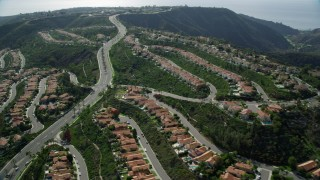 AX0159_183 - 8K stock footage aerial video flying by hillside homes in Laguna Niguel, California