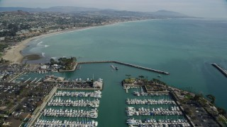 AX0159_194 - 8K stock footage aerial video flying over boats at Dana Point Harbor, and approach the shore in Dana Point, California
