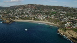 AX0159_203 - 8K stock footage aerial video flying by homes beside Three Arch Bay Beach in Laguna Beach, California