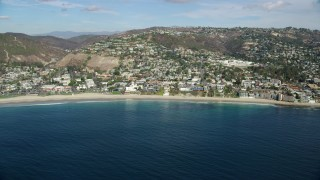 AX0159_212 - 8K stock footage aerial video approaching beach and beachfront and hillside homes, Laguna Beach, California