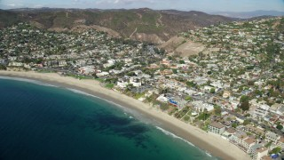 AX0159_213 - 8K stock footage aerial video flying over ocean, beach and houses, Laguna Beach, California