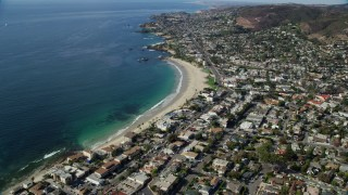 AX0159_214 - 8K stock footage aerial video flying away from beach and over coastal community, Laguna Beach, California