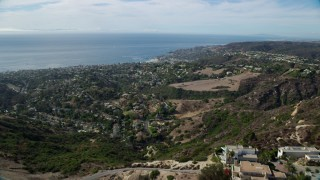AX0159_215 - 8K stock footage aerial video flying over hill to reveal coastal community below, Laguna Beach, California