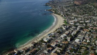 AX0159_218 - 8K stock footage aerial video flying over homes and Main Beach Park, Laguna Beach, California